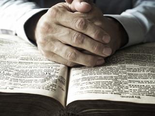 hands praying on bible