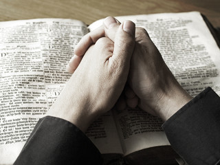 hands praying on bible