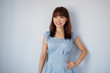 Cute Asian woman isolated on blue background.