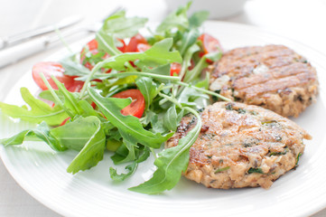 Ground fish patty with arugula tomato salad