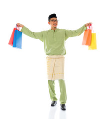 Traditional Malay male shopping and jumping in joy during hari r