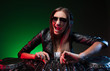 Female DJ. Happy young female DJ in sunglasses playing music and