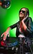 Female DJ at work. Beautiful young female DJ in headphones spinn