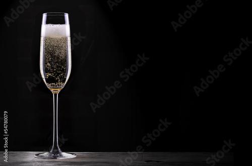 Leinwanddruck Bild glass of champagne isolated on black background