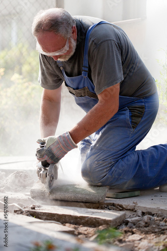 bearded man with glasses and gloves sawing stone with grinder