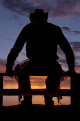 Silhouette cowboy sit fence