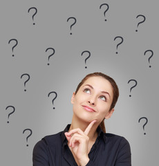 Thinking woman looking up on many questions mark on grey backgro