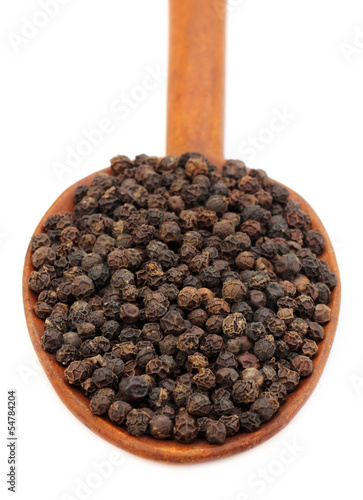 Black peppers on a wooden spoon