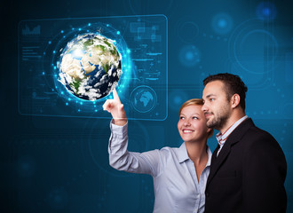 Young couple touching high-tech 3d earth panel