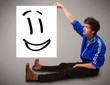 Young boy holding smiley face drawing