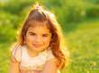 Cute little girl on green field