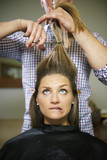 nervous woman in hairdresser shop cutting long hair
