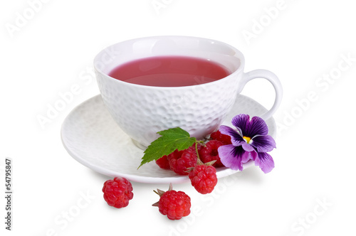 White mug with berry tea, raspberry and pansies