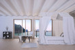 White bedroom interior with canopy bed and seascape view