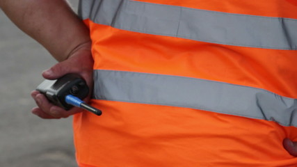 Clumsy security with walky-talky in orange uniform standing