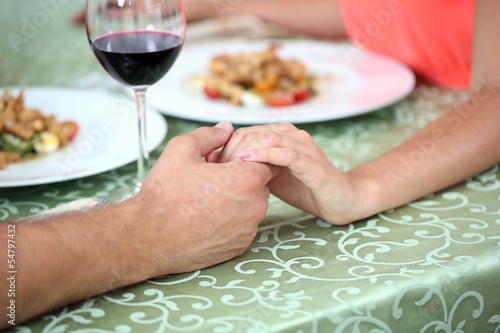 Hands of romantic couple over a restaurant table