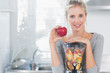 Happy woman leaning on her juicer full of fruit and holding red