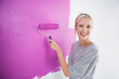 Laughing woman painting her wall in pink