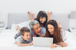 Cheerful family lying on bed using their laptop