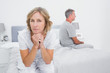 Thoughtful couple sitting on different sides of bed having a dis