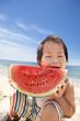 夏の海でスイカを食べる子供