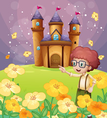 A boy pointing near the flowers in the hill with a castle