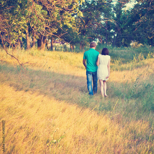 happy young couple walking on a path in the woods