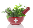 Porcelain mortar with medicine cross and fresh herbs