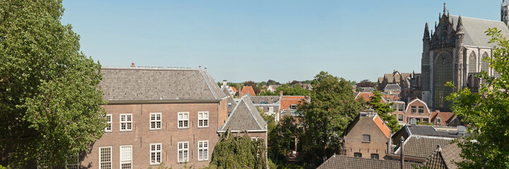 Panoramic photo of roofs and church of dutch city Leiden in summ