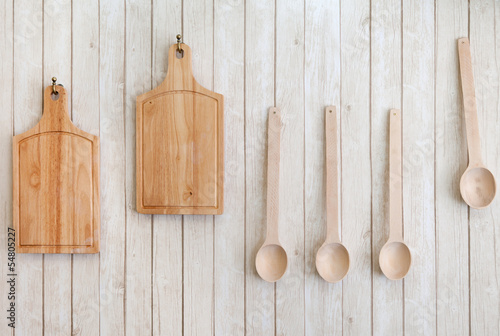 cutting boards and wooden spoons hanging on the wall