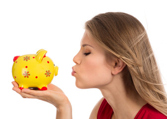 Portrait of young woman kissing piggy bank, isolated on white