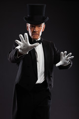 Magician making mysterious gestures. Wearing black suit and hat.
