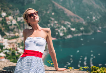 Beautiful young woman and view of Positano, Italy