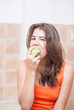 Beautiful teenage girl biting an apple