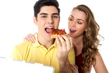 Young couple sharing a pizza slice poster