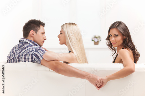 Love triangle. Beautiful young women holding hands with men sitt