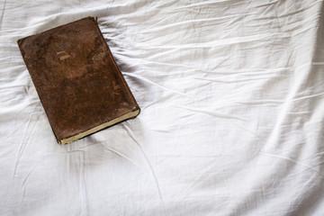 libro viejo sobre una sábana arrugada