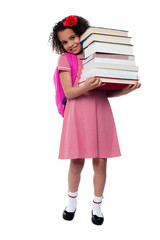 Cute little schoolgirl carrying stack of books