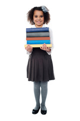 Active school child carrying stack of books