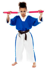 Young girl in karate uniform holding nunchucks