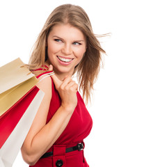 Pretty smiling fashionable female shopper with shopping bags