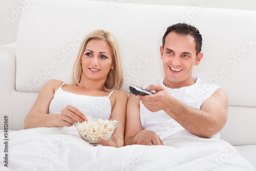 Couple Relaxing On Bed With A Popcorn Watching Television