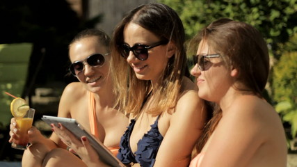 Young attractive girls with tablet on vacation