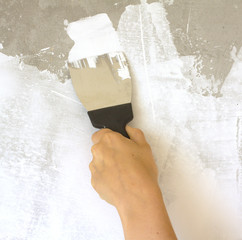 Woman's hand with a spatula wall plasters in room during repair