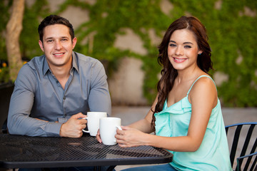 Attractive Latin couple having some coffee together at a terrace