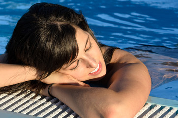 Woman relax at evening into swimming pool