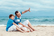 Father and son sitting on sea