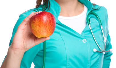 Young lady doctor is holding a red apple