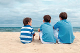 Three brothers are sitting on beach