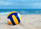 ball is lying on sand near sea